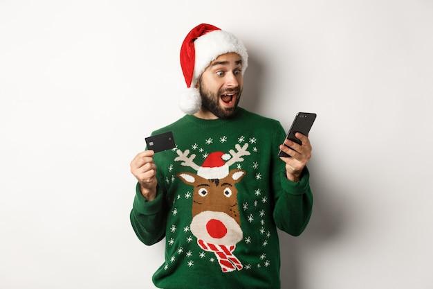Online winkelen en wintervakantie concept man kijkt opgewonden naar mobiele telefoon terwijl hij inte...