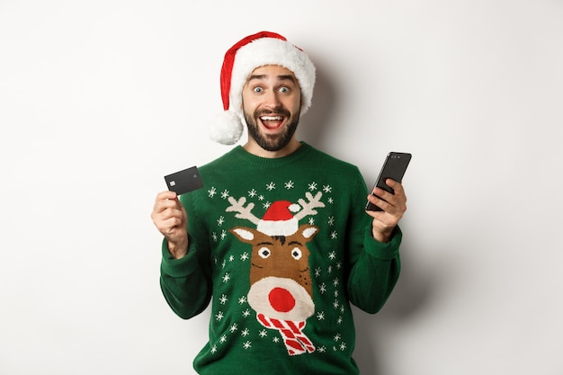 Online winkelen en wintervakantie concept. verrast man in kerstmuts, met mobiele telefoon en creditcard, staande in trui op witte achtergrond