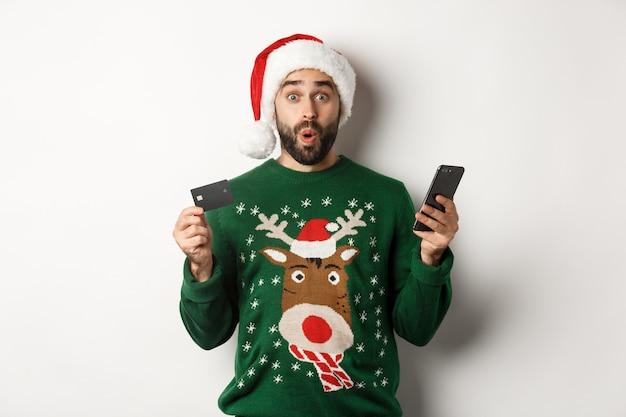 Online winkelen en wintervakantie concept. verrast man koopt cadeaus op internet met mobiele telefoon en creditcard, staande in kerstmuts op witte achtergrond.