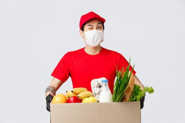 Online winkelen, eten bezorgen en coronavirus pandemisch concept. aziatische bezorger brengt klant online winkelbestelling, koerierspakket met verse boodschappen, werknemer bezorgt producten