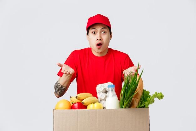 Online winkelen, eten bezorgen en internetwinkels concept. geschokte, bezorgde bezorger met rode pet en t-shirt die klaagt over het verkeerde adres van de klant, schouderophalend in de buurt van kruidenierswaren