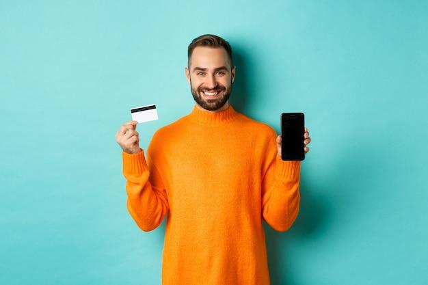 Online winkelen. gelukkige aantrekkelijke kerel die het scherm van de mobiele telefoon en creditcard toont, tevreden glimlachend, die zich over lichte turkooise muur bevindt