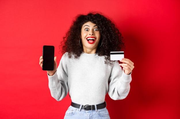 Online winkelen. gelukkige jonge vrouw die plastic creditcard en leeg telefoonscherm toont, kondigt promo-aanbieding aan, staande op rode achtergrond