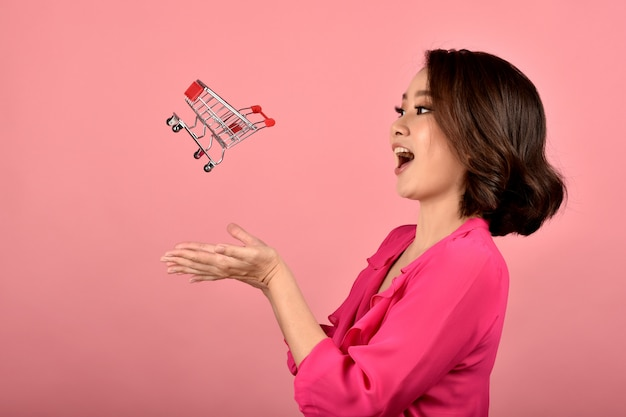 Online winkelen, happy aziatische vrouw en mini grappige winkelwagentje trolley