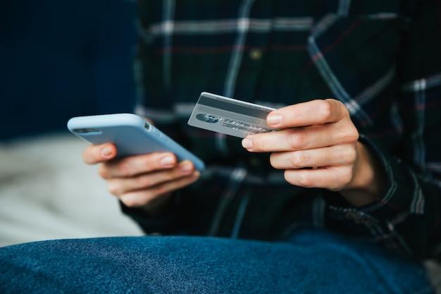 Online winkelen in internet-concept. vrouw die creditcard en smartphone gebruikt