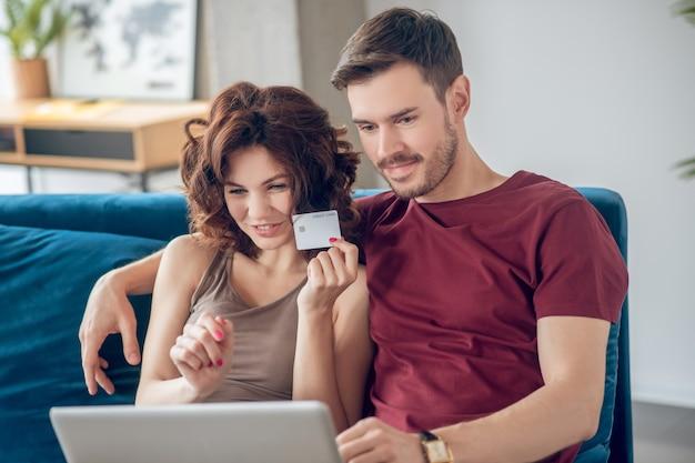 Online winkelen. jong koppel aanbrengen op de bank en producten online kiezen