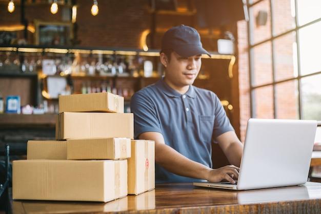 Online winkelen jonge start kleine bedrijven in een kartonnen doos op het werk.