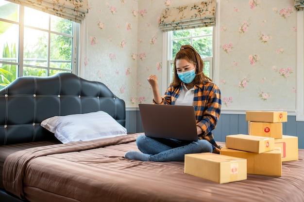 Online winkelen jonge vrouwen hebben succes met het starten van een klein bedrijf in een kartonnen doos op het werk.