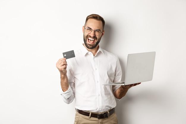 Online winkelen. knappe man die creditcard toont en laptop gebruikt om op internet te bestellen, staande op een witte achtergrond.