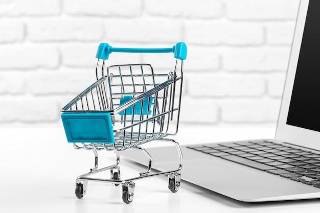 Online winkelen mini-winkelwagentje en laptop