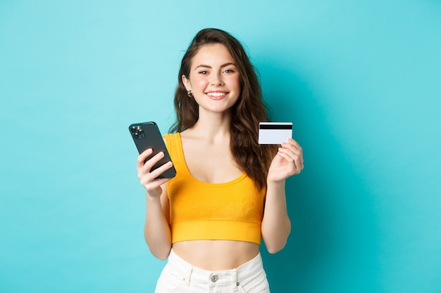 Online winkelen. mooie vrouw die zich klaarmaakt voor de zomervakantie, kaartjes boekt met creditcard en smartphone-app, staande over blauwe achtergrond