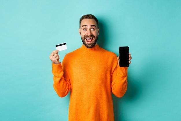Online winkelen. opgewonden man met mobiel scherm en creditcard, verbaasd glimlachend, staande over een turkooizen achtergrond.