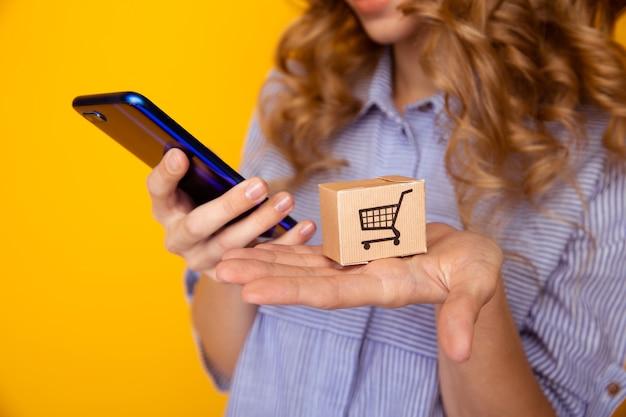 Online winkelen. papieren dozen in de hand van de vrouw en telefoon. levering dienstverleningsconcept.
