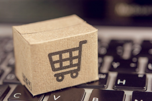 Online winkelen - papieren dozen of pakjes met een winkelwagentje-logo op een laptoptoetsenbord. boodschappenservice op het online web en biedt levering aan huis.