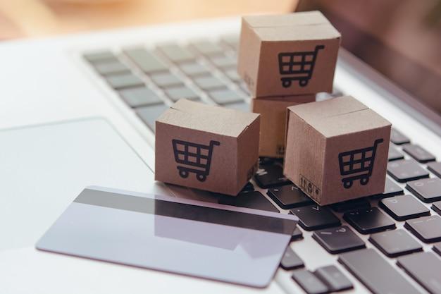 Online winkelen - papieren dozen of pakket met een winkelwagenlogo en creditcard op laptop toetsenbord. boodschappenservice op het online web en biedt bezorging aan huis.
