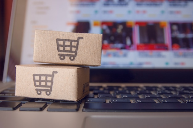 Online winkelen: papieren dozen of pakket met een winkelwagentje-logo op een laptoptoetsenbord. shopping-service op het online-web en biedt levering aan huis.