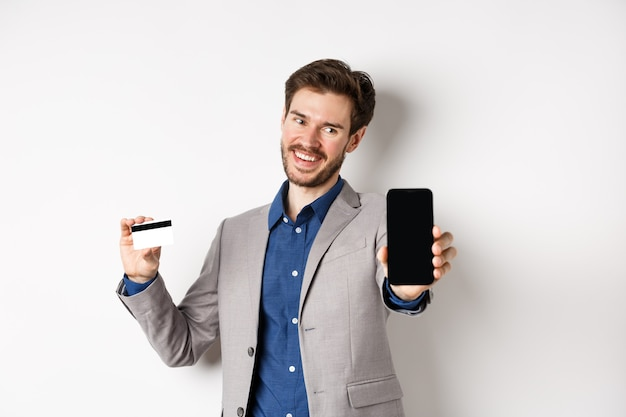 Online winkelen. succesvolle zakenman die plastic creditcard houdt en het mobiele scherm toont, tevreden glimlacht, geld verdient, witte achtergrond.