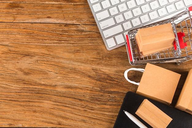 Online winkelen thuis concept. dozen in een winkelwagentje op een laptoptoetsenbord. online winkelen is een vorm van elektronische handel waarmee consumenten via internet rechtstreeks goederen van een verkoper kunnen kopen