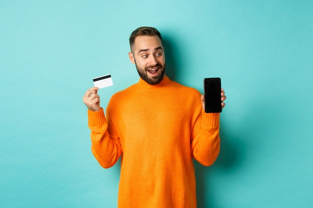 Online winkelen. verbaasde man die creditcard gebruikt en mobiel scherm laat zien, onder de indruk, staande tegen een lichtblauwe achtergrond