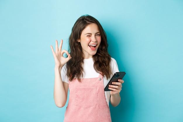 Online winkelen. vrolijk schattig meisje dat naar je knipoogt, glimlacht en een goed teken toont na het gebruik van de smartphone-app, het aanbevelen van internetwinkel of sociale media-pagina, blauwe achtergrond.