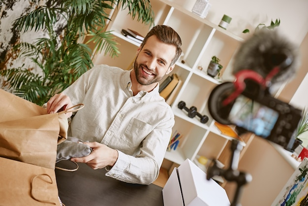 Online winkelen vrolijke en jonge mannelijke blogger die zijn nieuwe aankopen online op een statief laat zien