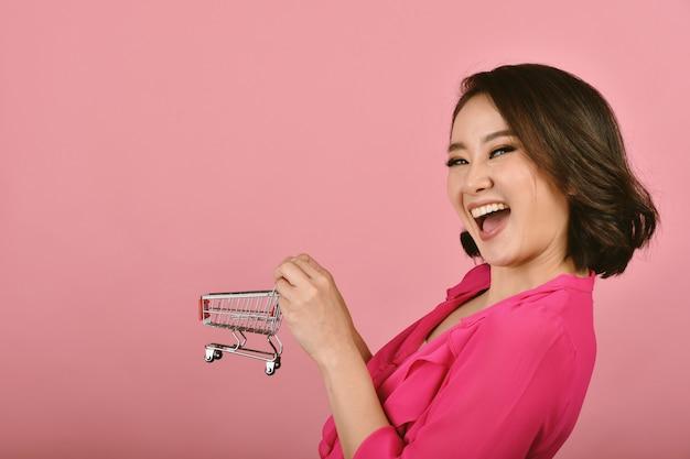 Online winkelend, gelukkige aziatische vrouw die grappig boodschappenwagentjekarretje houden