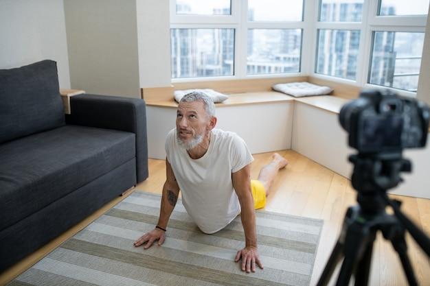 Online zelfstudie. een volwassen man in een wit t-shirt die een online yoga-tutorial opneemt