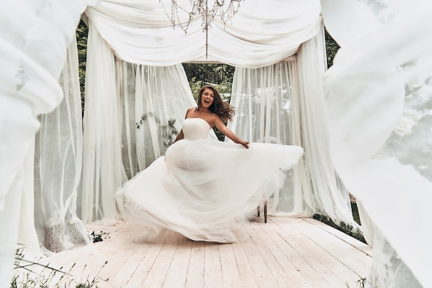 Onmogelijk om haar geluk te verbergen. volledige lengte van aantrekkelijke jonge vrouw in trouwjurk die schreeuwt tijdens het dansen in het huwelijkspaviljoen buitenshuis