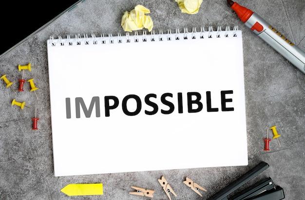Onmogelijke tekst op een wit notitieboekje met spelden, stift en nietmachine op een betonnen tafel