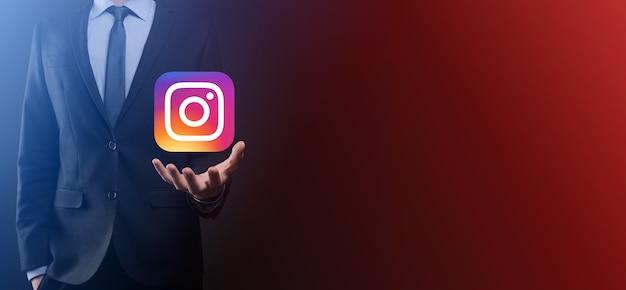 Onok, oekraïne - 14,2021 juli: zakenman houdt, klikt, instagram-pictogram in zijn handen. sociaal netwerk. globaal netwerk en gegevensklantverbinding. internationaal netwerk.