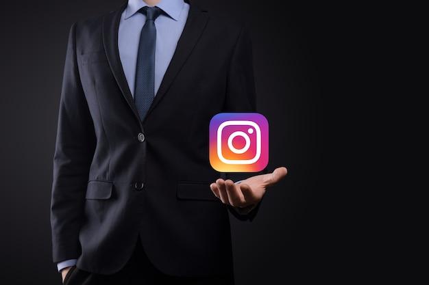 Onok, oekraïne - 14,2021 juli: zakenman houdt, klikt, instagram-pictogram in zijn handen. sociaal netwerk. wereldwijd netwerk en gegevensklantverbinding. internationaal netwerk.