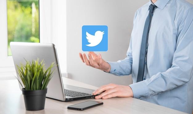 Onok, oekraïne - 14,2021 juli: zakenman houdt, klikt, twitter-pictogram in zijn handen. sociaal netwerk. wereldwijd netwerk en gegevensklantverbinding. internationaal netwerk.