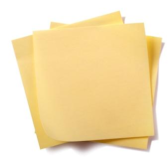Onordelijke stapel gele kleverige postnota's die op wit worden geïsoleerd