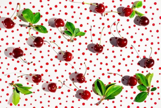 Onregelmatig patroon met zoete kersen en bladeren op polka dot achtergrond