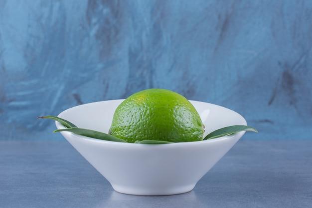 Onrijpe citroen in een kom, op het donkere oppervlak