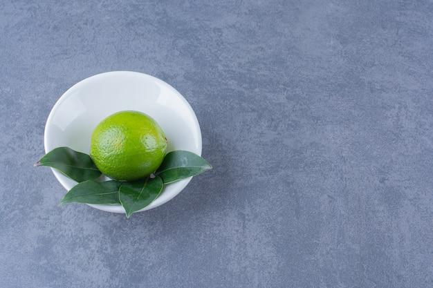 Onrijpe citroen in een kom op marmeren tafel.