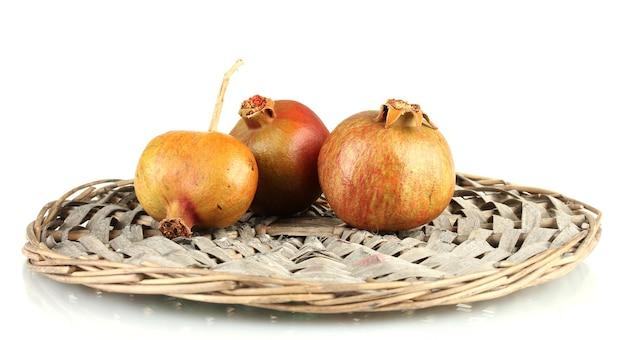 Onrijpe granaatappels op rieten mat die op wit wordt geïsoleerd