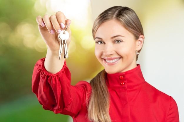 Onroerend goed. blije makelaar. aantrekkelijke jonge vrouw met sleutels