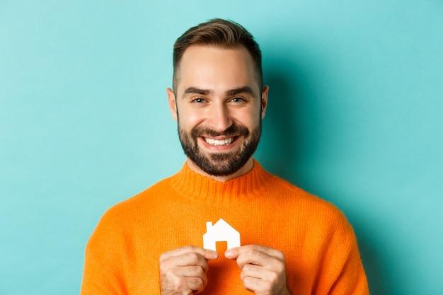 Onroerend goed concept. gelukkig jonge man op zoek naar huis te huur, papier huis glimlachen te houden