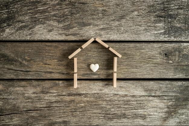 Onroerend goed concept met een hart in het frame van een huis op een tafel in hoge hoekmening.