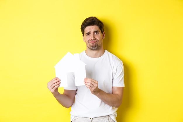 Onroerend goed concept ontstemde jonge man die papieren huismodel toont en grimassen van streek die over...