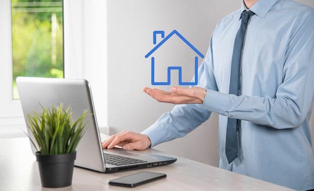 Onroerend goed concept, zakenman die een huispictogram houdt. huis aan de kant. vastgoedverzekering en veiligheidsconcept. gebaar van de mens en symbool van huis beschermen.