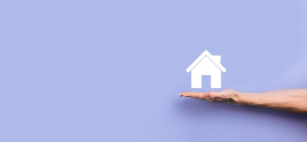 Onroerend goed concept, zakenman die een huispictogram houdt. huis aan de kant. vastgoedverzekering en veiligheidsconcept. gebaar van man en symbool van huis beschermen