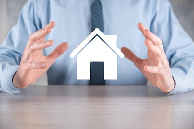 Onroerend goed concept, zakenman houden een huisje. huis aan kant. onroerend goed verzekering en veiligheidsconcept. beschermend gebaar van man en symbool van huis.