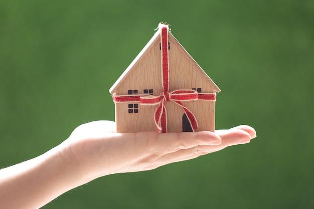 Onroerend goed en cadeau nieuw huis concept, vrouw hand met model huis met rood lint op natuurlijke groene achtergrond