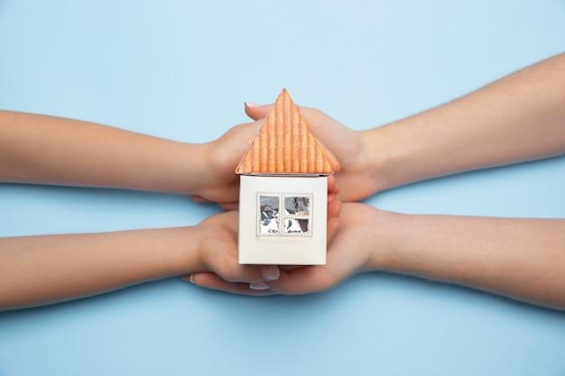 Onroerend goed en eco concept - close-up foto van menselijke handen met huis op blauwe achtergrond. presentatie van verhuizen, nieuw huis, onroerend goed. nieuw leven voor familie, huisvesting.