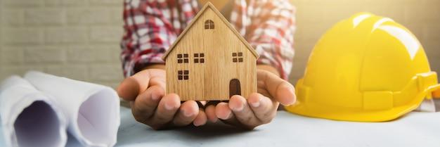 Onroerend goed en hypotheek concept engineer holding house om de beste eigendommen en investeringen te presenteren