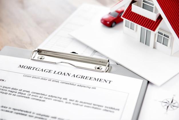 Onroerend goed hypotheek lening overeenkomst papier met huis model op tafel