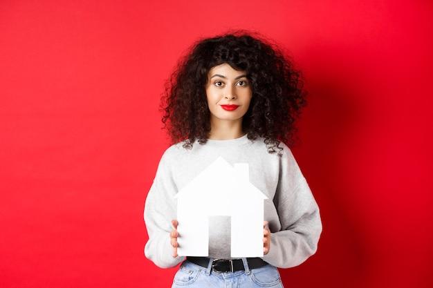 Onroerend goed. jonge kaukasische vrouw in vrijetijdskleding die een uitgesneden huis toont, onroerend goed koopt of appartement huurt, staande op rode achtergrond