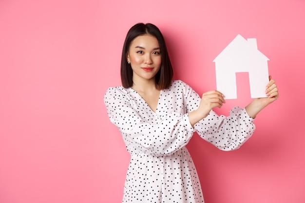 Onroerend goed mooie aziatische vrouw die papieren huismodel demonstreert en naar camera zelfverzekerde advertentie kijkt...